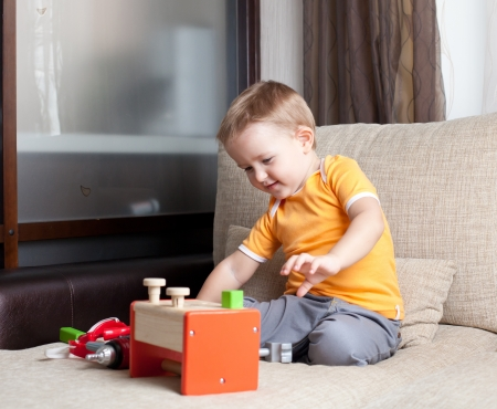 adorable child playing with wooden building toys at home photo