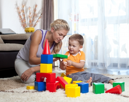 assembling: cute mother and child boy playing together indoor