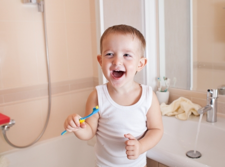 kid or child brushing teeth in bathroom photo