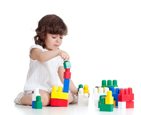 building blocks: child girl with construction set over white background