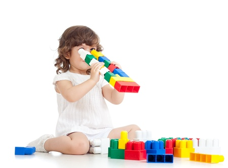 inventive kid with construction set toy over white background photo