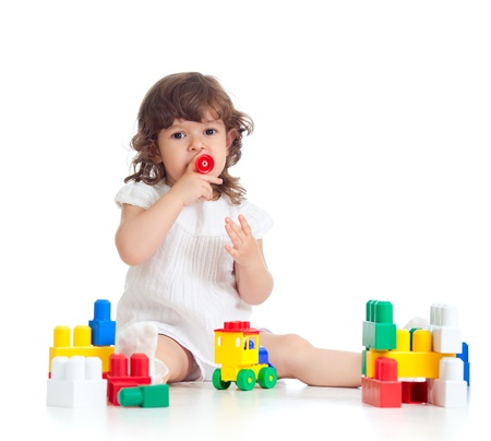 inventive kid girl with construction set toy over white background photo