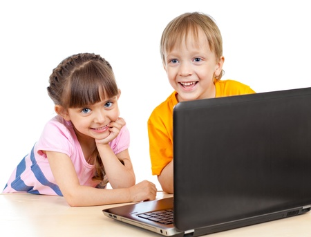 happy children boy and girl using a laptop photo