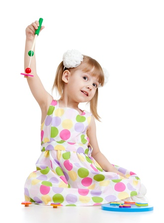 Funny kid girl playing with toys, isolated over white photo