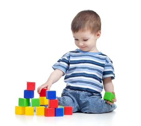 cheerful kid boy with construction set over white background photo