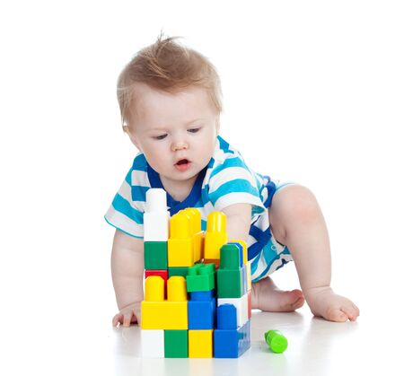 cheerful child boy with construction set over white background photo