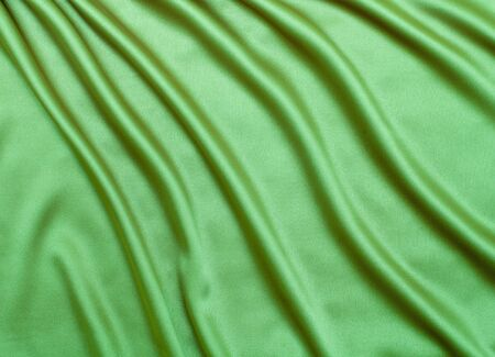 green satin or silk fabric background photo