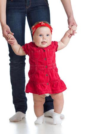 first step: little baby girl doing ersten Schritt mit Hilfe der Mutter