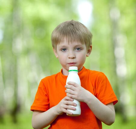 Cute child holding bottle with milk photo