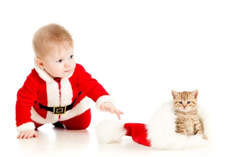 christmas baby reaching out hand for cat in a santa claus hat photo