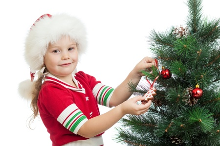 pretty preschool child decorating Christmas tree isolated on white photo