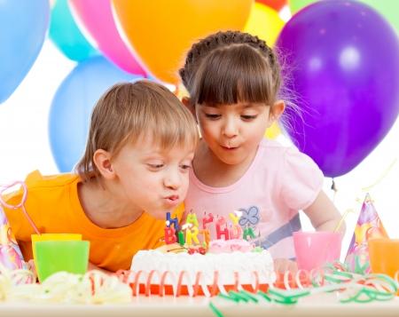 tortas cumpleaÑos: niños celebrando la fiesta de cumpleaños y soplando las velas en la torta Foto de archivo