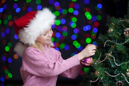 Christmas happy child girl decorating x-mas tree over  bright festive background photo