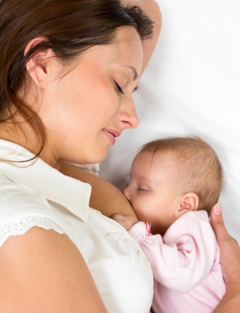 close-up portrait of  relaxed mother breast feeding her baby infant photo