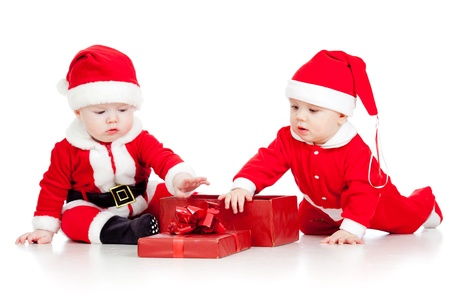 two funny small kids in Santa Claus clothes with gift box photo