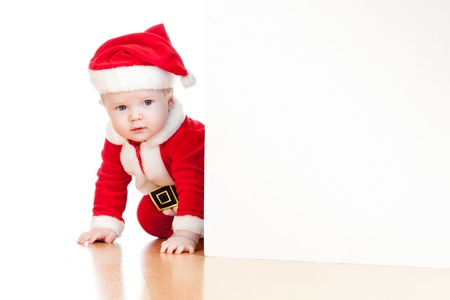 innocent: small Santa claus child looking from behind the placard Stock Photo