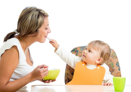 loving mom spoon feeding her playful child girl isolated on white Stock Photo - 15259674