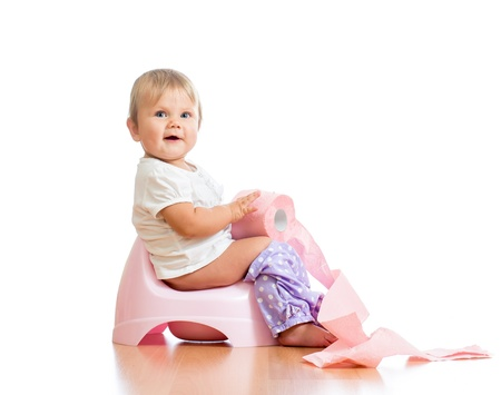 toilet paper: smiling baby sitting on chamber pot with toilet paper roll Stock Photo