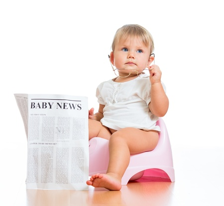 baby wardrobe: funny child girl sitting on chamberpot with eyeglasses and newspaper