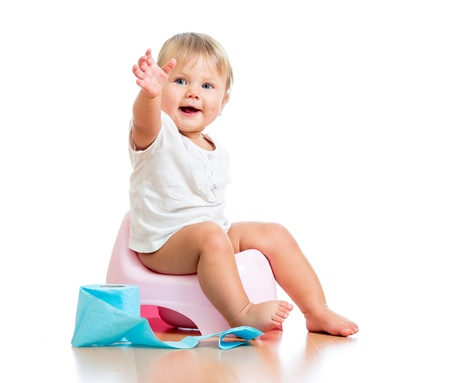 potty training: smiling baby sitting on chamber pot with toilet paper roll Stock Photo