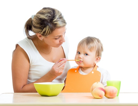mother feeding her baby girl by spoon photo