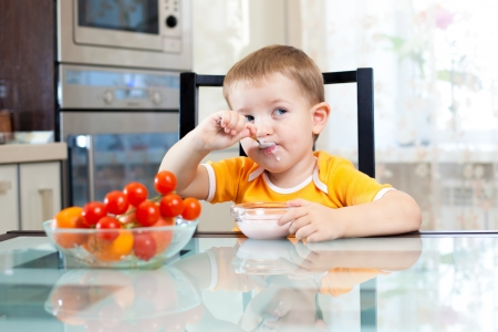 child boy eating healthy food in kitchen photo