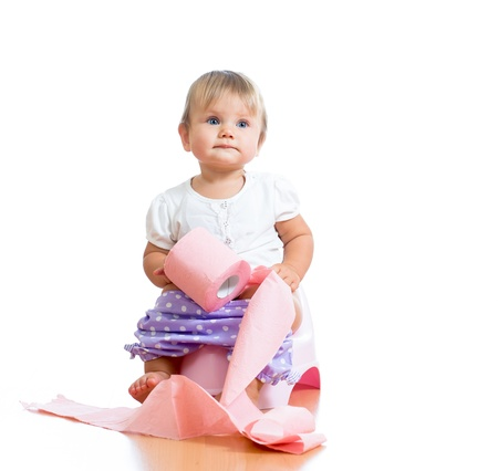 chamber pot: funny baby sitting on chamber pot with toilet paper roll Stock Photo