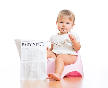 pissing: funny baby girl sitting on chamberpot with eyeglasses and newspaper Stock Photo