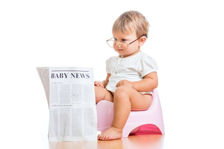 funny child girl reading newspaper on chamberpot photo