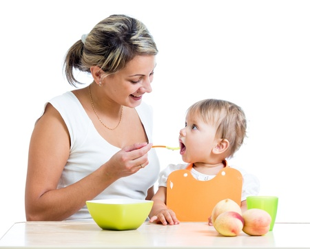 two parents: mother feeding her baby girl by spoon Stock Photo