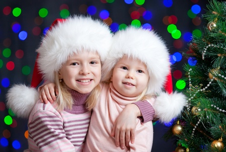 kids sisters Santa Claus hugging over bright festive background photo