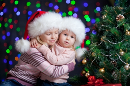 baby xmas: embracing children girls in Santa Claus hat on bright festive background Stock Photo