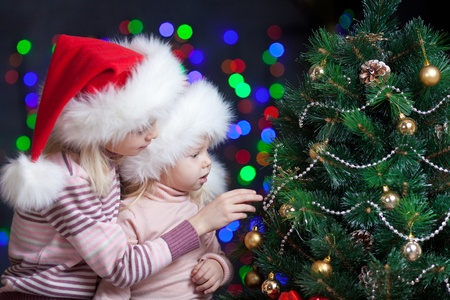 Santa Claus kids near Christmas tree over bright festive background photo
