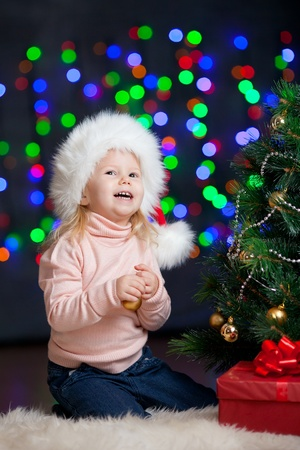 pretty preschool girl decorating Christmas tree over bright festive background photo