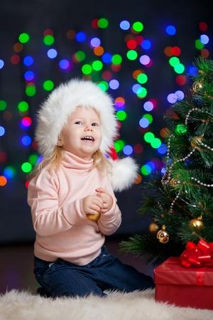 pretty preschool girl decorating Christmas tree over bright festive background Stock Photo - 15361466