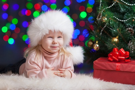 baby girl dressed in Santa Claus hat lying near Christmas tree with gift photo