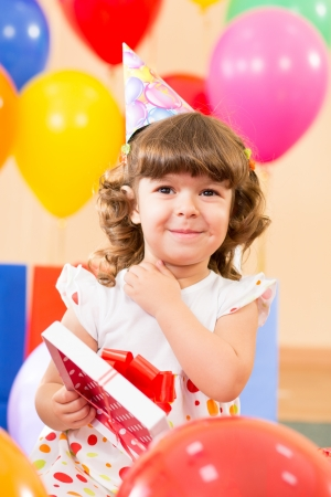 curly headed: pretty girl  with colorful balloons and gifts on birthday party Stock Photo