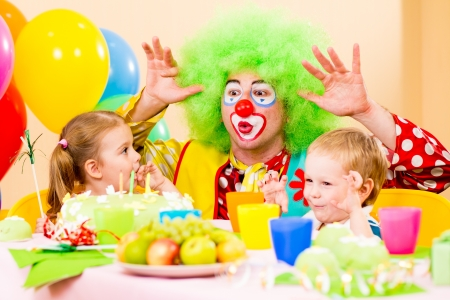 happy kids with clown on birthday party photo