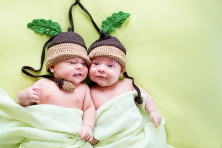 two twins brothers babies weared in acorn hats photo