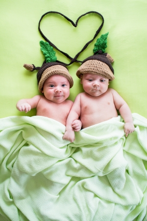 newborn baby boy: two twins brothers babies weared in acorn hats