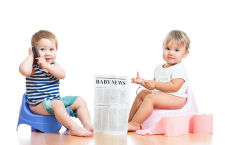 funny children with newspaper and pda on chamberpot photo
