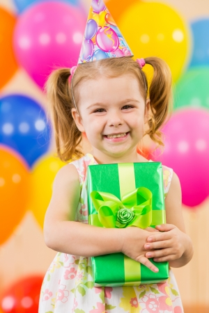 children celebration: Cute girl  with colorful balloons and gifts