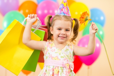 pretty child girl with colorful balloons and gifts on birthday party photo