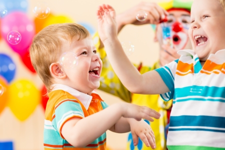 inflatable: joyful kids with clown on birthday party Stock Photo