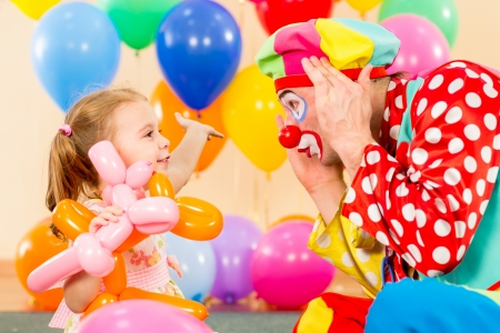 entertainment funny: happy child girl and clown playing on birthday party
