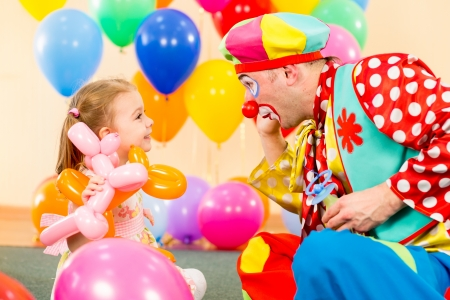 birthday adult: happy child girl and clown playing on birthday party