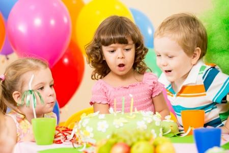 enfants c�l�brent la f�te d'anniversaire et souffler les bougies sur le g�teau photo