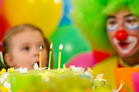 festive cake with three candles and kid with clown on background photo