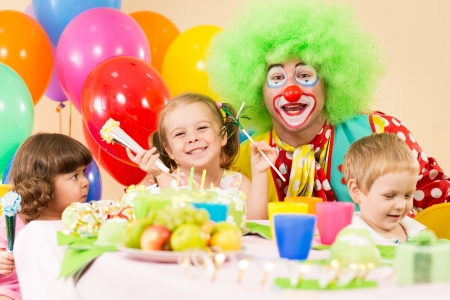 children celebrating birthday party with clown photo