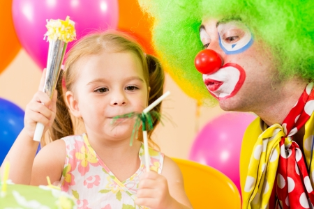 happy child girl playing with clown on birthday party photo